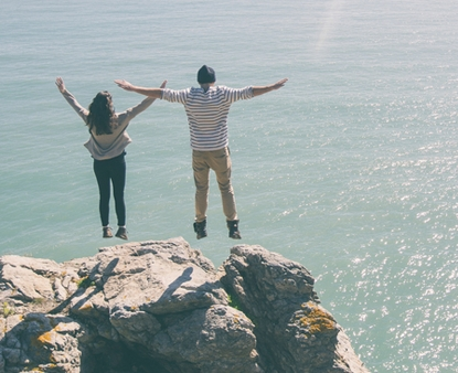 A couple on top of cliff looking over the ocean.